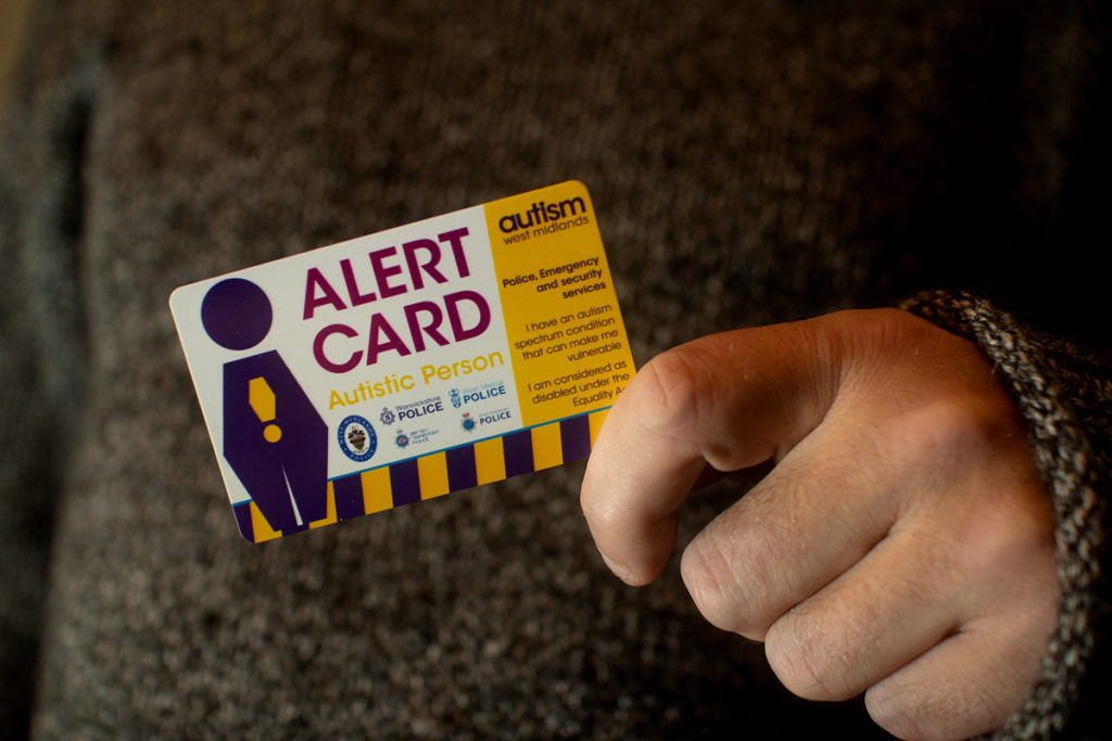 Someone holding an Autistic Person Alert Card